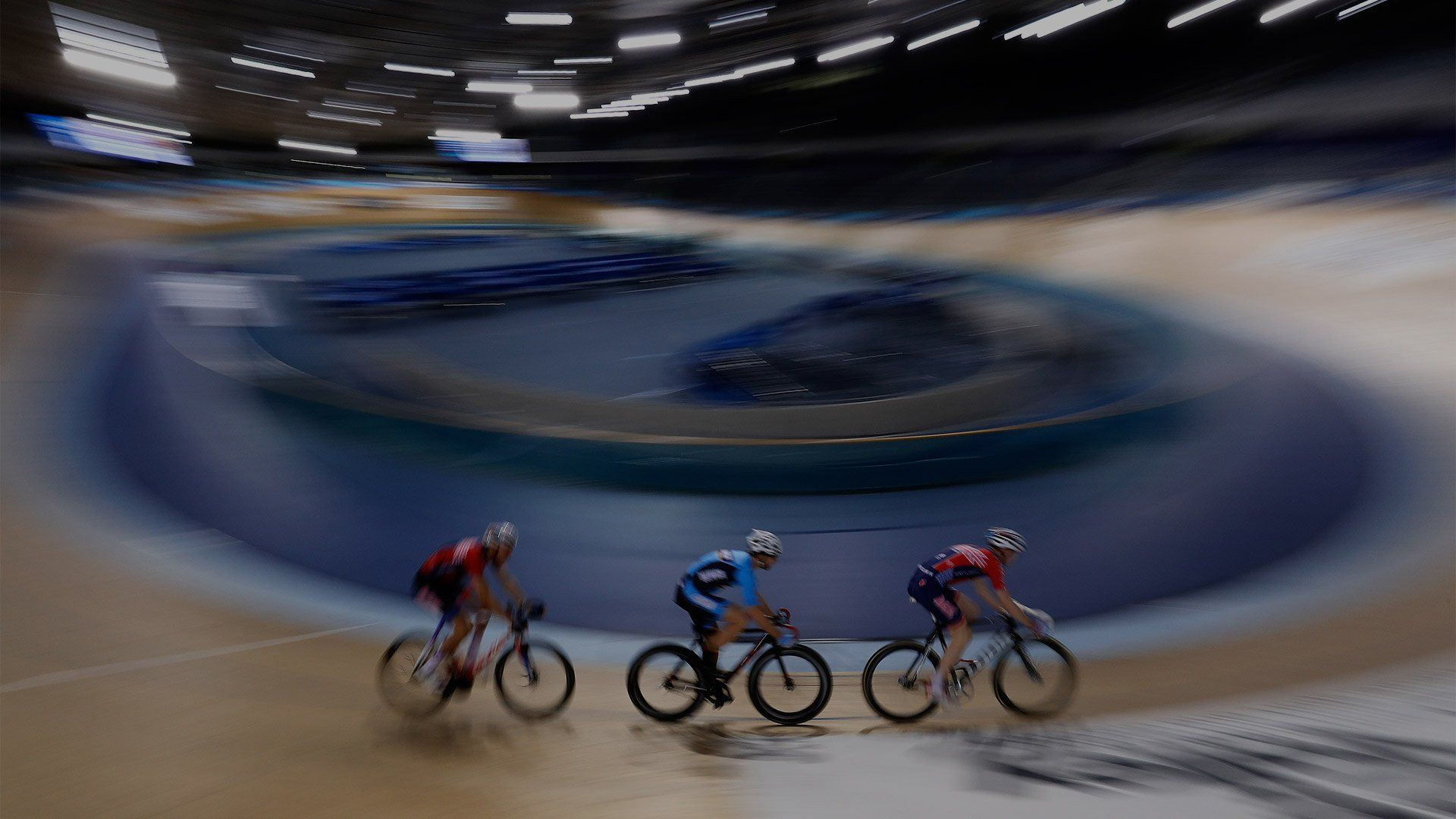 Three cyclists ride around a velodrome; the cyclists are in sharp focus, with everything else blurred.